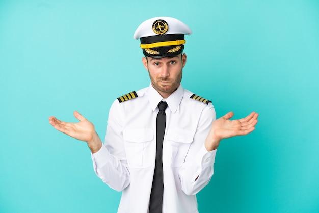 Vliegtuig kaukasische piloot geïsoleerd op blauwe achtergrond die twijfels heeft terwijl hij zijn handen opsteekt
