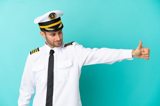Vliegtuig kaukasische piloot geïsoleerd op blauwe achtergrond met een duim omhoog gebaar