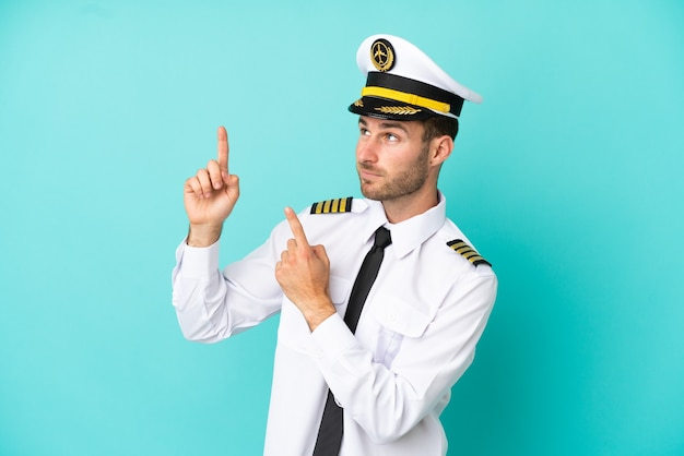 Vliegtuig kaukasische piloot geïsoleerd op blauwe achtergrond wijzend met de wijsvinger een geweldig idee