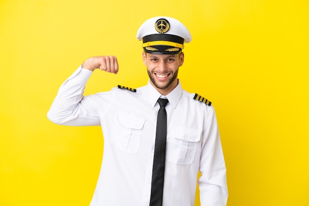 Vliegtuig kaukasische piloot geïsoleerd op gele achtergrond doen sterk gebaar