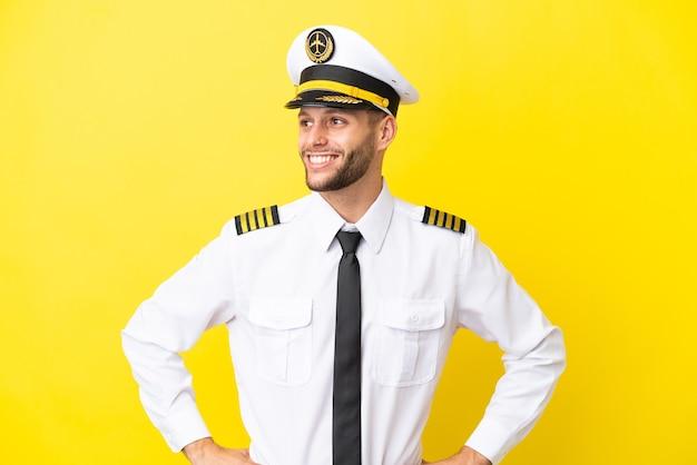 Vliegtuig kaukasische piloot geïsoleerd op gele achtergrond poseren met armen op heup en lachend