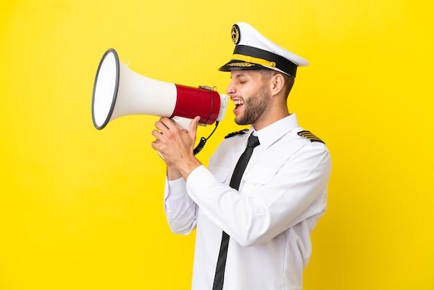 Vliegtuig kaukasische piloot geïsoleerd op gele achtergrond schreeuwen door een megafoon
