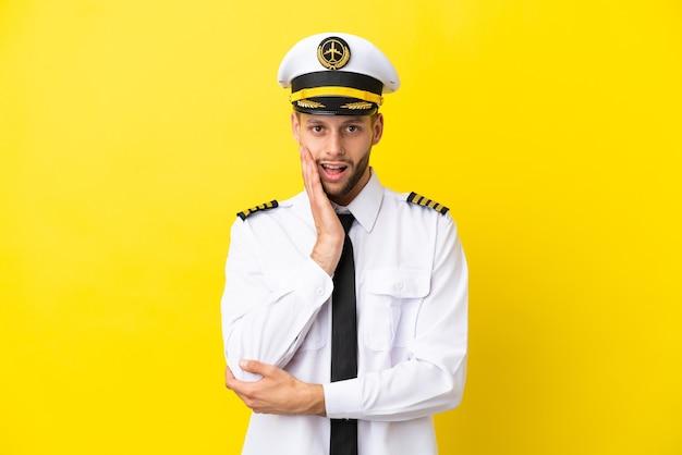 Vliegtuig kaukasische piloot geïsoleerd op gele achtergrond verrast en geschokt terwijl hij naar rechts kijkt