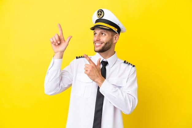 Vliegtuig kaukasische piloot geïsoleerd op gele achtergrond wijzend met de wijsvinger een geweldig idee