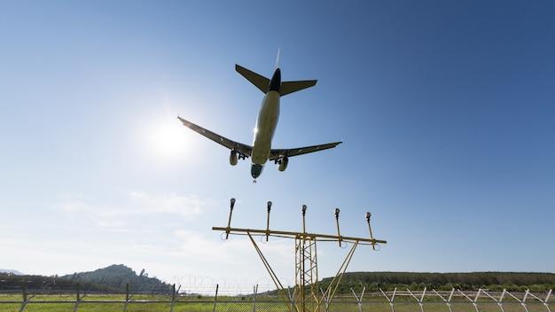 Vliegtuig met chassis dat boven tegen een blauwe hemel, navigatie of landend licht vliegt dat naar de startbaan op de achtergrond leidt, groothoek