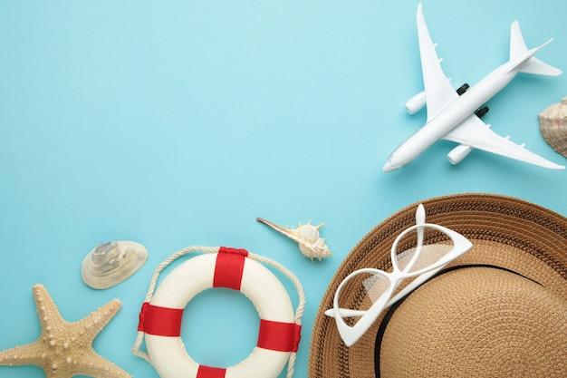 Vliegtuig met reizigerstoebehoren op blauwe achtergrond. reis concept. bovenaanzicht