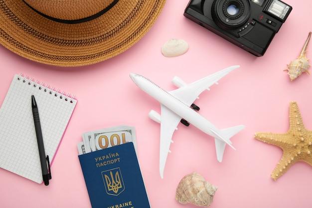 Vliegtuig met reizigerstoebehoren op roze achtergrond. reis concept. bovenaanzicht
