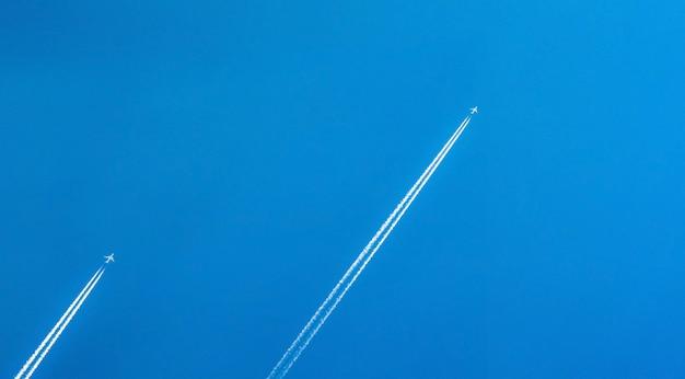 Vliegtuig met witte condensatiesporen. jet op heldere blauwe hemel met dampsleep. reizen per vliegtuig concept. slepen uitlaatgas van vliegtuigmotor.