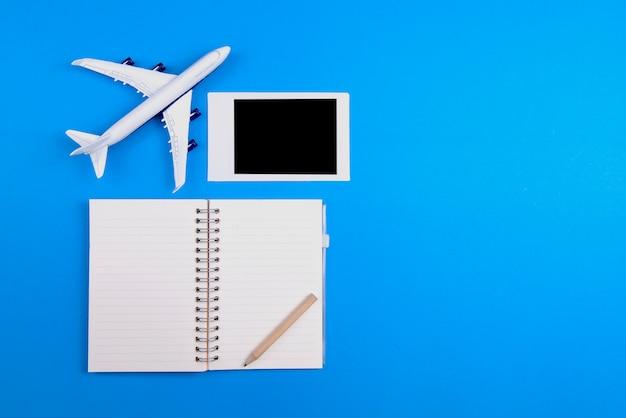 Vliegtuig model notebook potlood en fotolijst geplaatst op een blauwe achtergrond toerisme en reizen