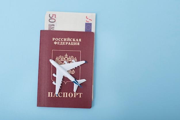 Vliegtuig op de cover van een russisch paspoort. euro. reisconcept. blauw oppervlak