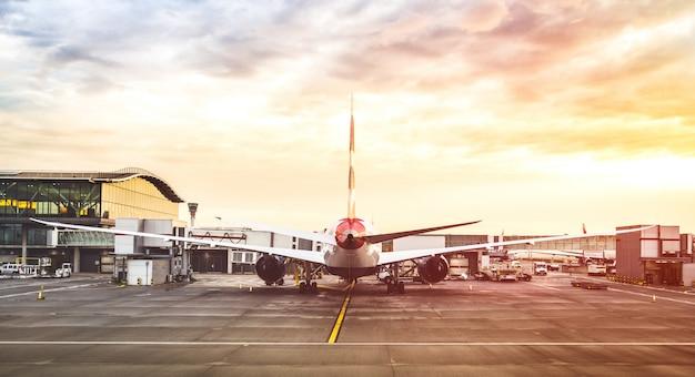 Vliegtuig op luchthaven met veelkleurige zonsondergangfilter