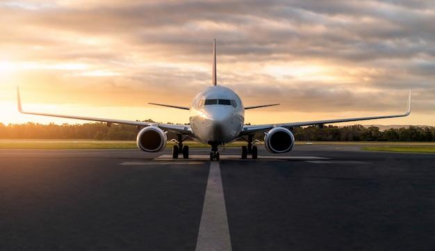 Vliegtuig op luchthavenbaan bij zonsondergang