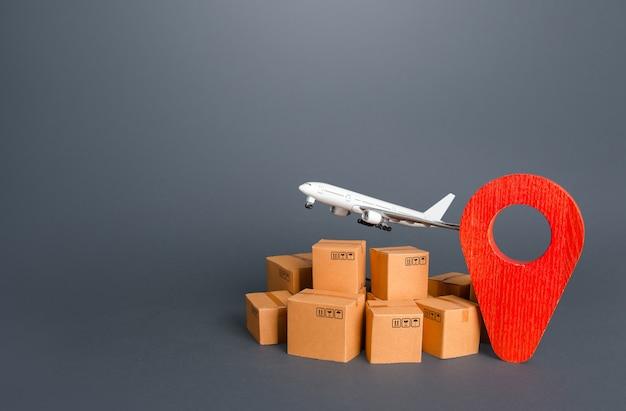 Vliegtuig over kartonnen dozen en rode positie-locatiepin bezorgdiensten van zendingen