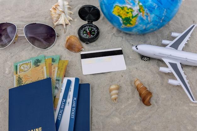 Vliegtuig, paspoort, aardebol en kaartjes op zand
