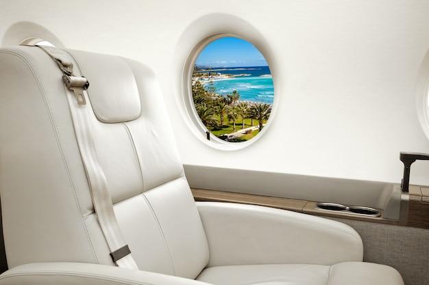 Vliegtuig patrijspoort met uitzicht op zee en strandresort, vlucht per business class