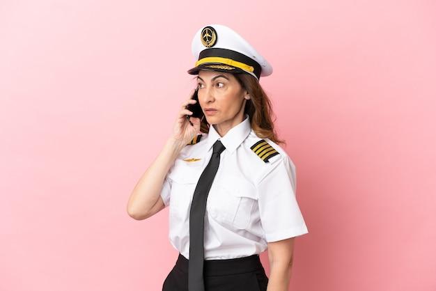 Vliegtuig piloot vrouw van middelbare leeftijd geïsoleerd op roze achtergrond die een gesprek voert met de mobiele telefoon