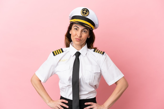 Vliegtuig piloot vrouw van middelbare leeftijd geïsoleerd op roze achtergrond lachen