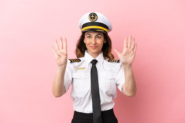 Vliegtuig piloot vrouw van middelbare leeftijd geïsoleerd op roze achtergrond tellen negen met vingers