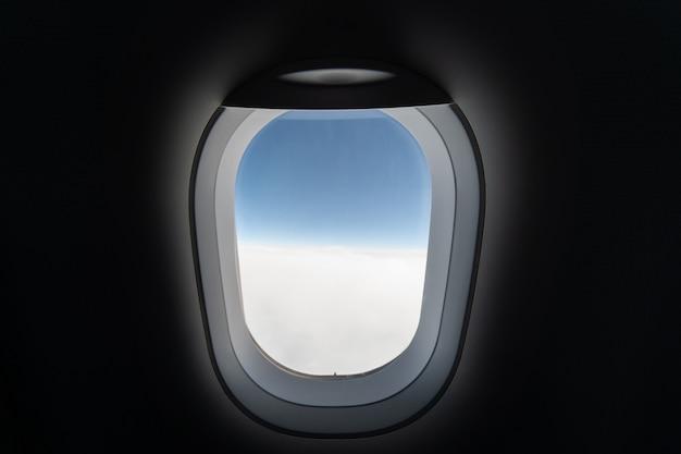 Vliegtuig raam uitzicht op bewolkte hemel en aarde. mooi landschap van vliegtuigcabine. vliegen zonder vliegangst, incidenten en turbulentie.