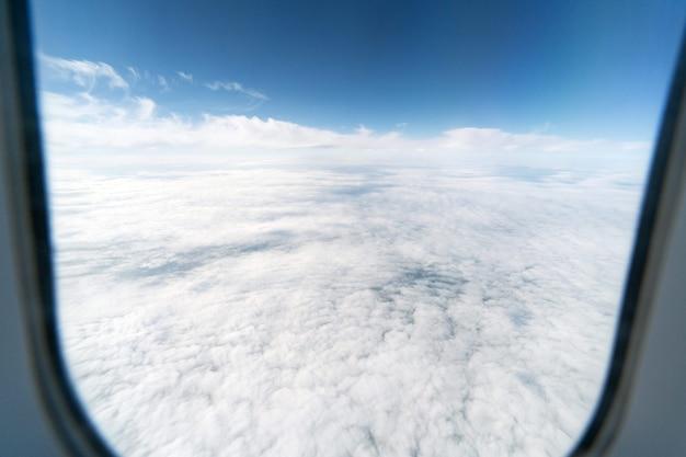 Vliegtuig raam uitzicht op bewolkte hemel en aarde