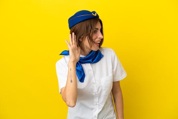 Vliegtuig stewardess vrouw geïsoleerd op gele achtergrond luisteren naar iets door hand op het oor te leggen