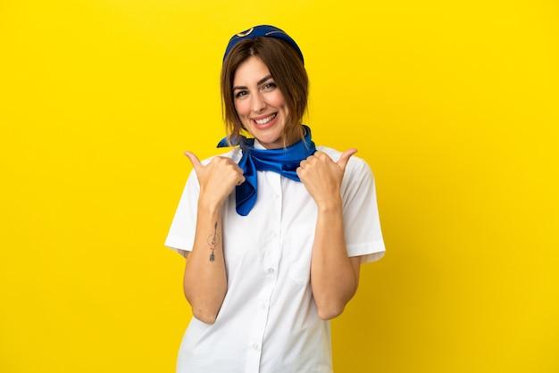 Vliegtuig stewardess vrouw geïsoleerd op gele achtergrond met duim omhoog gebaar en lachend