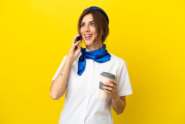 Vliegtuig stewardess vrouw geïsoleerd op gele achtergrond met koffie om mee te nemen en een mobiel
