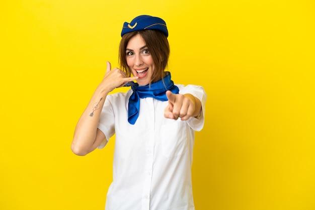 Vliegtuig stewardess vrouw geïsoleerd op gele achtergrond telefoon gebaar maken en naar voren wijzen