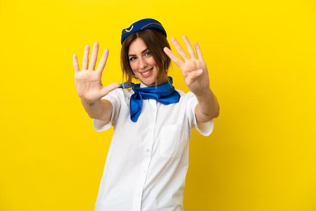 Vliegtuig stewardess vrouw geïsoleerd op gele achtergrond tellen negen met vingers