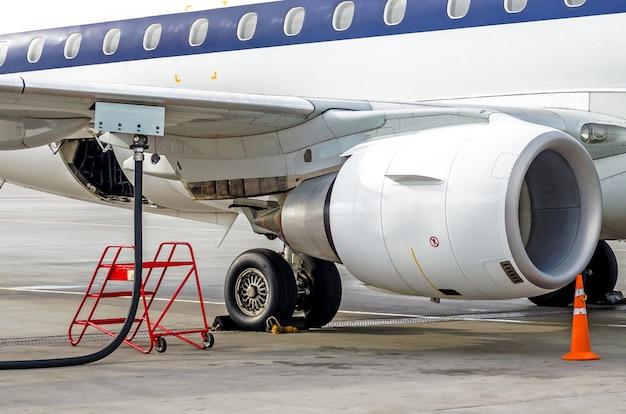 Vliegtuig tanken, zicht op de vleugel, slang, motor. luchthaven service.