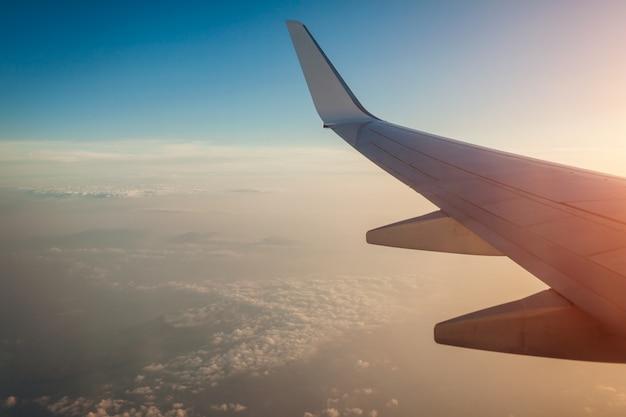 Vliegtuig venster weergave van wolken en eilanden omgeven door zee en vliegtuig vleugel. reizend
