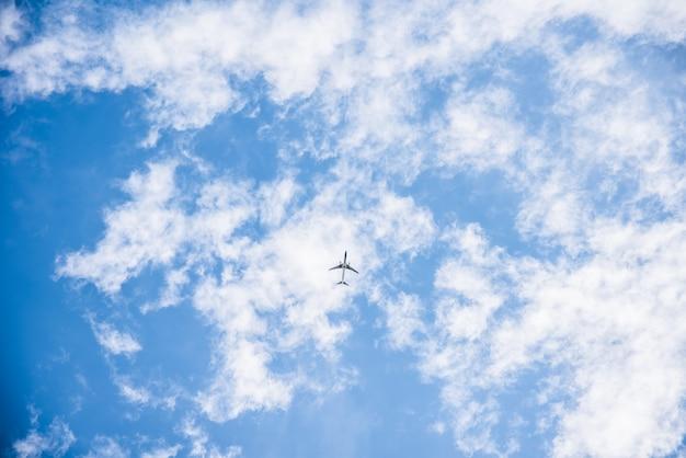 Vliegtuig vliegt in de blauwe lucht