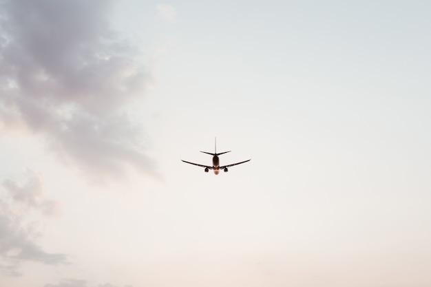 Vliegtuig vliegt in de lucht bij zonsondergang met roze paarse wolken
