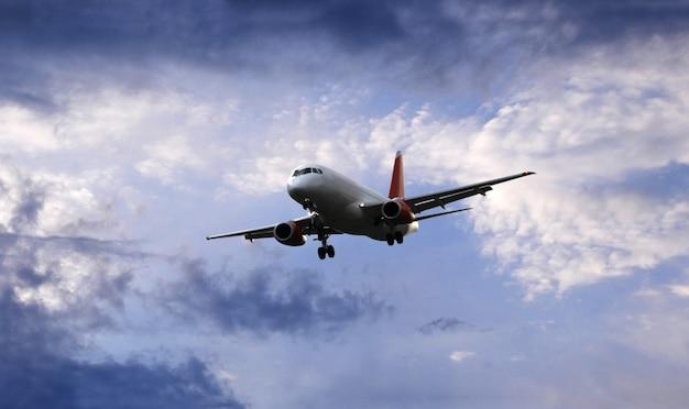Vliegtuig vliegt onder mooie avondwolken vooraanzicht vliegtuig met het chassis voor de landing op de luchthaven