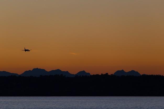 Vliegtuig vliegt over heuvels en zee bij zonsondergang