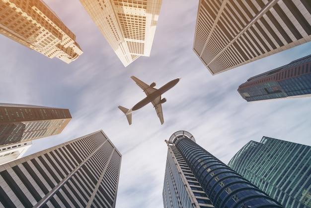Vliegtuig vliegt over zakelijke stadsgebouwen en wolkenkrabbers