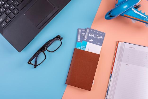 Vliegtuig, vliegtickets, paspoort, laptop en telefoon met een bril.