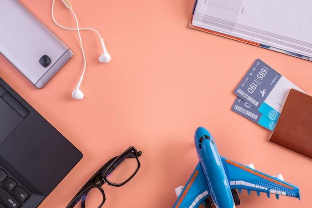 Vliegtuig, vliegtickets, paspoort, laptop en telefoon met koptelefoon op roze
