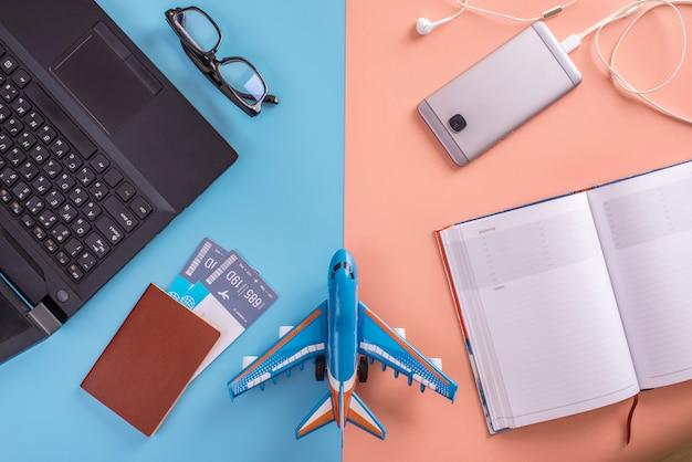 Vliegtuig, vliegtickets, paspoort, laptop en telefoon met koptelefoon.