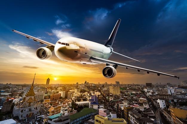 Vliegtuig voor vervoer dat over de stad op mooie zonsondergangachtergrond vliegt
