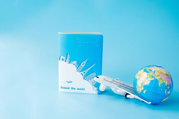 Vliegtuig, wereldbol en paspoort op blauwe achtergrond. zomer of vakantie concept.
