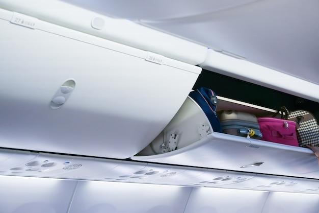Vliegtuigcabine met bagageruimtes, bagage klaar voor vertrek aan boord van vliegtuigen
