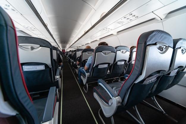 Vliegtuigcabine stoelen met passagiers. economy class van nieuwe goedkoopste low-cost luchtvaartmaatschappijen zonder vertraging of annulering van de vlucht. reisreis naar een ander land.