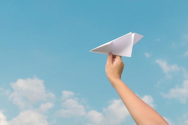 Vliegtuigdocument in kinderenhand en blauwe hemel