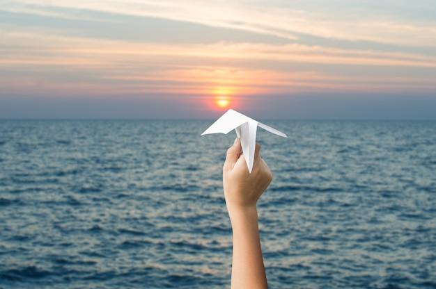 Vliegtuigdocument in kinderenhanden en zonsondergang, vooruit aan het doelconcept.