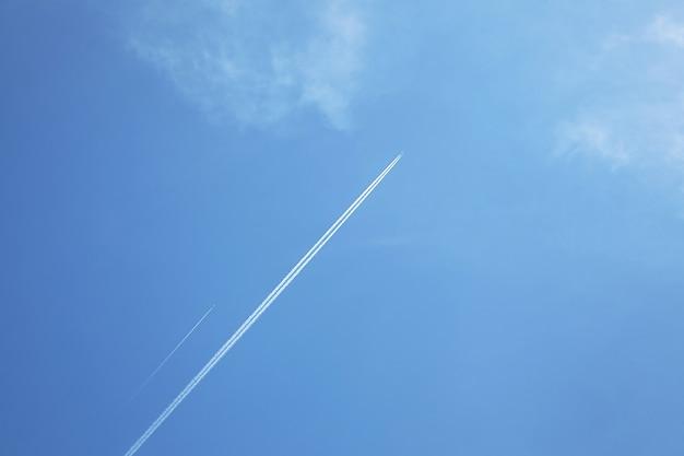 Vliegtuigen in de blauwe lucht met witte wolken, het vliegtuig laat sporen na
