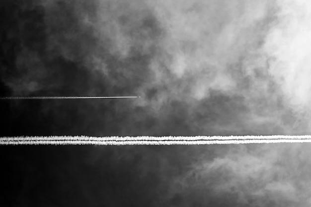 Vliegtuigen in donkere hemel met witte wolken