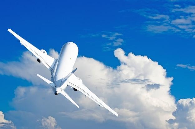 Vliegtuigen klimmen vlucht tegen de stapelwolken in de lucht