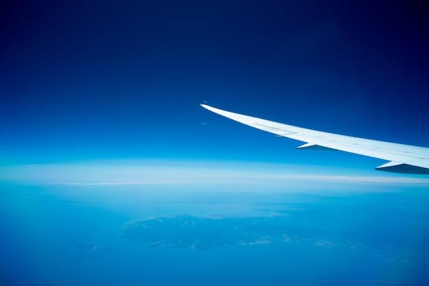 Vliegtuigen vliegen boven de clound en de blauwe lucht. mooi uitzicht vanuit het vliegtuigraam.