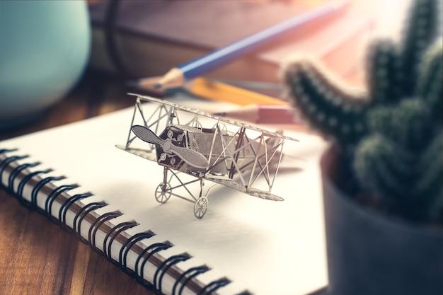 Vliegtuigjager op open onderwijsboek met abstract licht, het concept van de onderwijsontwerper.